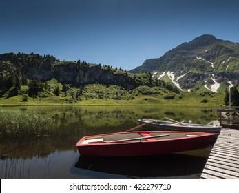 A view of boats that anchor at the bridge of Koerbersee lake around the village Schroecken in Bregenzerwal, region Vorarlberg, Austria