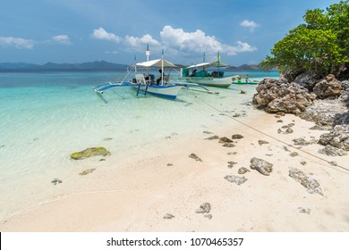 View of boats at tropical beach on the Bulog Dos Island, Busuanga, Philippines. Beautiful tropical island with sand beach, palm trees. Travel concept