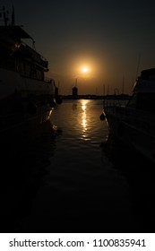 View of boats and windmill in Mandraki harbor in City of Rhodes, sunset (Rhodes, Greece)