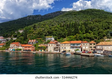View of Boka Kotorska with pier and boats in Lepetance, Montenegro.
