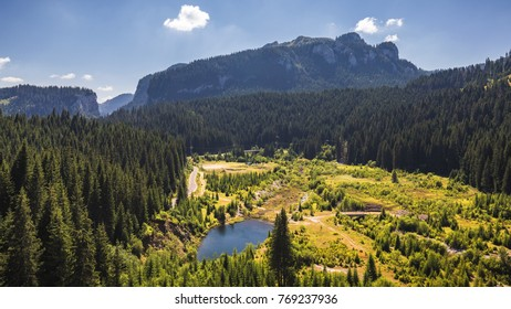 View to Bolboci lake from the damb with carpathian mountains at the background, Sinaia, Romania.