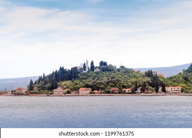 View of Book Kotorska from the ferry - hill covered with greenery and calm water