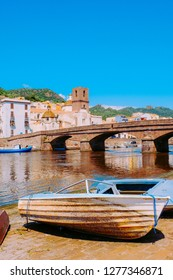 View of Bosa Cathedral and the 19th-century bridge over the Temo river with an old fishing boat on the foreground. Bosa - one of small colourful italian villages on Sardinia, Italy.