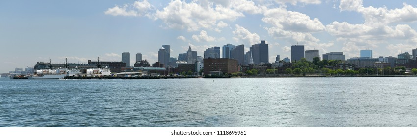 A view of Boston Massachusettes from across the water on a day with sun and clouds