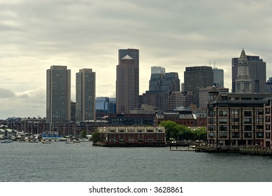 View of the boston skyline from boston harbor showing various skyscrapers from different eras. The sea is choppy and the sky cloudy