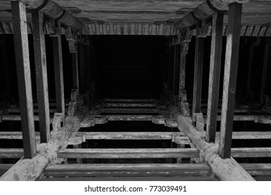 View from the bottom of a large wooden pillars in an old temple in Japan. Out of focus