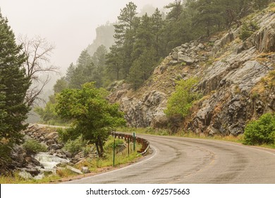 A view up Boulder Canyon Drive with Boulder Creek flowing on a rainy misty Colorado day. Photo: