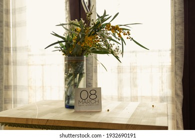 View of a bouquet of mimosas on a flowerpot and 8 march sign standing on a wooden table in front of a window - Shutterstock ID 1932690191