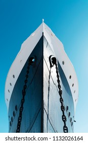 a view of the bow of a moored ship, painted white and navy, against the blue sky