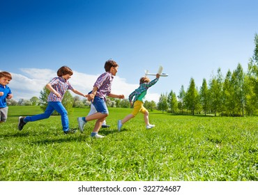View of boy with airplane toy and following him children running happily together during beautiful sunny weather in park