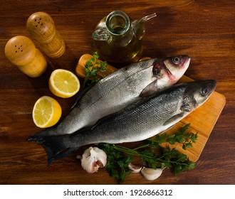 View of branzino fish on cutting board on wooden surface with fresh lemon, parsley, garlic and spices