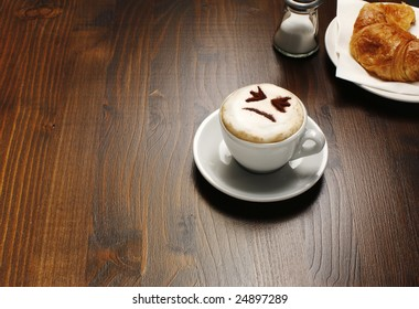 A view of a breakfast table with a cup of cappuccino that has a face showing in the foam