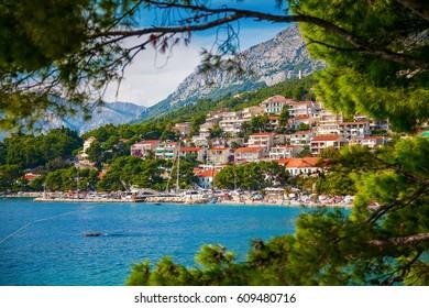 view of the Brela village through green pines, Makarska Riviera, Croatia