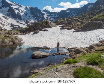 View from Bremer Hutte on man hiker standing in lake from melting snow tongues and snow-capped moutain peaks, lush green meadow, blue sky backgound. Late spring sunny afternoon, vibrant colors
