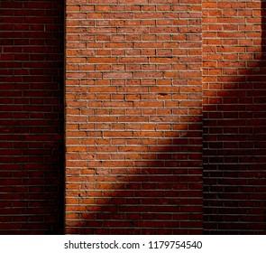 View at brick wall with shadow. Real hosue brick wall