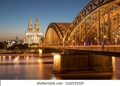 a view of the bridge and the cologne dome from the riverside by night