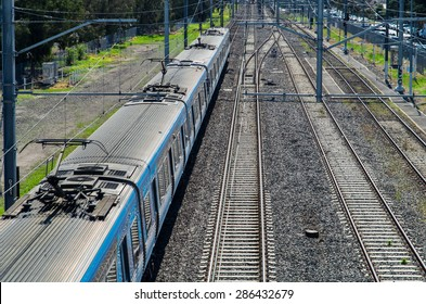 View from a bridge of an electric suburban train passing underneath.  The train is a Melbourne suburban train in Australia but no signage is visible on the train.