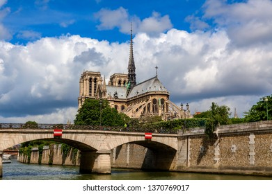 View of bridge over Seine river and famous Notre-Dame cathedral under beautiful sky in Paris, France.
