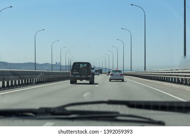 View of the bridge and the road through the windshield of the car. There are other cars on the road.