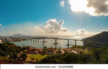 view of bridge (Terceira Ponte), Vila Velha city, Vitoria city and mountain in background. Blue sky.