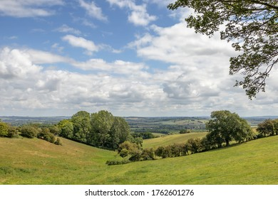 A view from Brill in Buckinghamshire looking out towards the Vale of Aylesbury, United Kingdom, sunny summer countryside scene with white fluffy clouds, blue skies and green rolling hills, v shaped