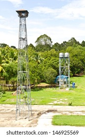 View of the broadcast tower and water tank, which is located in the grass near the tree