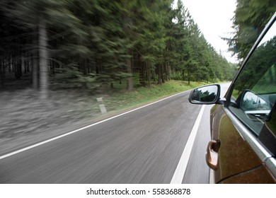 View from a bronze color car going through rainy forest
