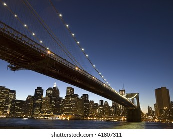 View of the Brooklyn bridge and south Manhattan from Brooklyn at dusk.