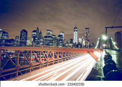 View of Brooklyn Bridge with traffic and Manhattan skyline by night