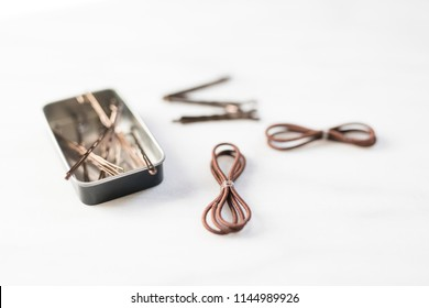 View of brown bobby pins, brown hair bands against a simple white background