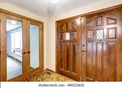 View to brown wooden enterance door. Tile floor and carpet floor in the next room. Glass transparent door