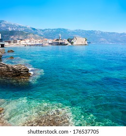 View of Budva Old Town with Clear Blue Water in Foreground. Montenegro, Balkans, Adriatic Sea. European Summer Resort in Mediterranean. Copy Space.