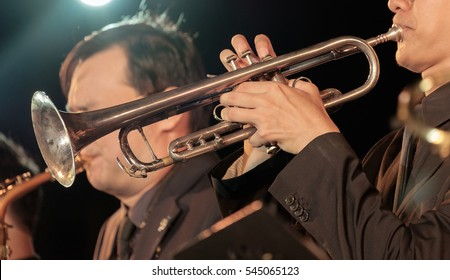 View of bugler blowing the trumpet in concert at night. Movement. Shallow depth of field.