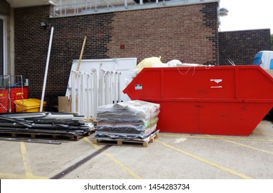 View of building material & full industrial bin for background use. Space to add text on concrete floor in front of metal shelfs, cardboard box, pallets and big red skip. Renovate, recycle concept.