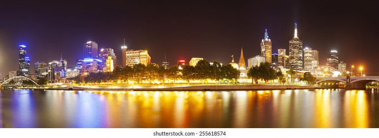View of buildings along the Yarra river in Melbourne at night, created by stitching multiple images