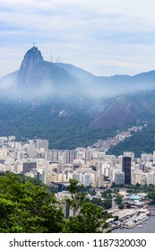 View of buildings in the  city of  Rio de Janeiro with Favelas in the hills with misty statue on mountain, Brazil , South America