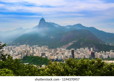 View of buildings in the  city of  Rio de Janeiro with Favelas in the mountain and  hills with mist and christ  statue on mountain, Brazil , South America