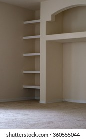 View of built in shelving units in modern vacant apartment living room.