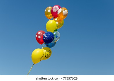 View of bunch of bright helium balloons flying high in bright blue sky.