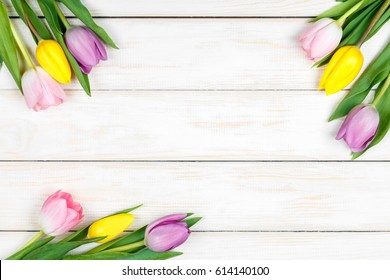 View of bunch of colored tulips lying on a white wooden background