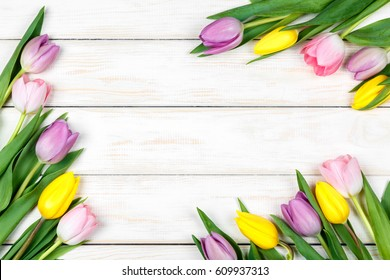 View of bunch of pink and yellow tulips lying on a white wooden background