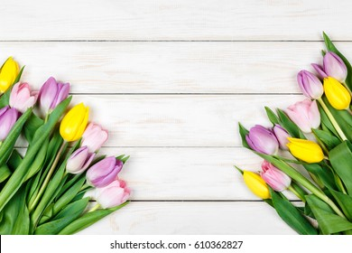 View of bunch of pink and yellow tulips on a white wooden background