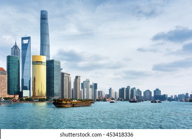 View from the Bund in Shanghai, China. The Shanghai Tower, the Shanghai World Financial Center and other skyscrapers of downtown are visible at left. Self-propelled barges on the Huangpu River.
