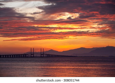The view of burning cloud over Penang Bridge during sunrise.