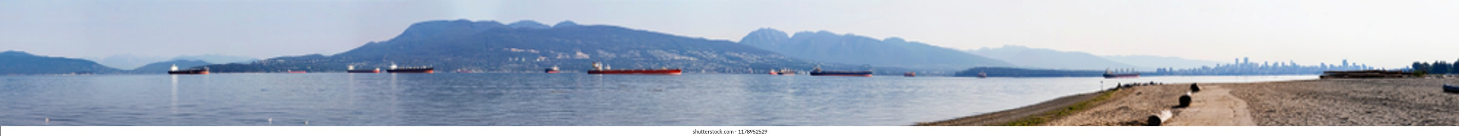 View of the Burrard Inlet looking towards English Bay, Vancouver, British Columbia, Canada; North shore mountains and downtown Vancouver visible from the Spanish Banks Beach Park