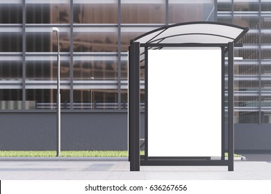 View of a bus stop with a blank vertical poster standing in a street near an office building. 3d rendering, mock up