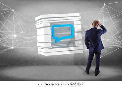 View of a Businessman in front of a wall with 3D rendering Blue Email symbol displayed in a sliced cube