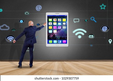 View of a Businessman in front of a wall with a tablet surrounding by app and social icon - 3d render