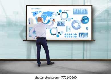 View of a Businessman in front of a wall writing on a business graph and chart interface - business concept