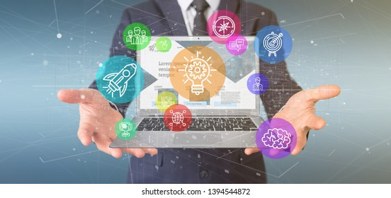 View of a Businessman holding a Cloud of colorfull start up icon bubble with a laptop 3d rendering